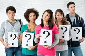 Teen students holding question mark signs